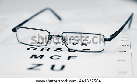 lear Black modern glasses on a eye sight test chart - stock photo