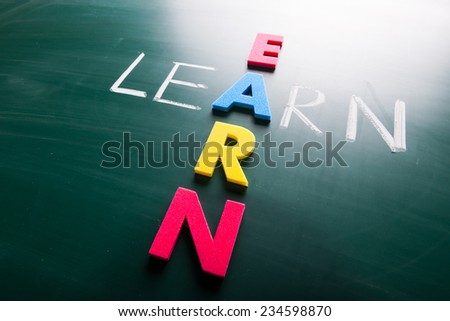 Learn and earn, words on blackboard with colorful alphabets.
