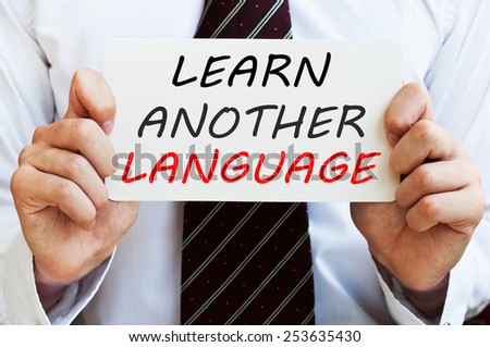 Learn another language. Man holding a card with a message written on it - stock photo