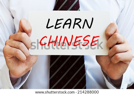 Learn Chinese - man wearing a shirt and a tie holding a signboard with a text on it. Education concept. - stock photo