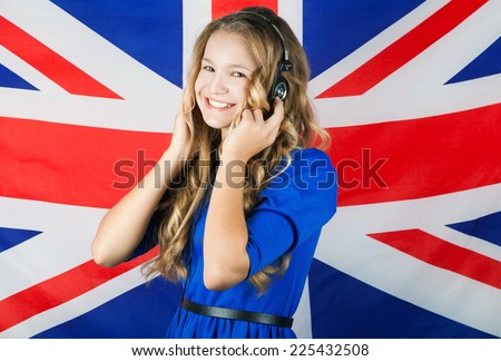 Learn English. Pretty school girl in headphones over british flag - stock photo