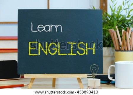 learn English -  text / message on the blackboard with the background of stationary on the office desk. the concept of foreign language education - stock photo