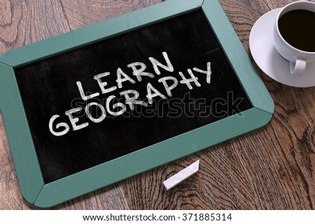 Learn Geography Handwritten on Blue Chalkboard. Business Concept. Composition with Chalkboard and Cup of Coffee. Top View Image. 3d Render. - stock photo