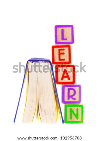 Learn Spelled Out Leaning on Open Book - stock photo