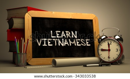 Learn Vietnamese - Chalkboard with Hand Drawn Motivational Quote, Stack of Books, Alarm Clock and Rolls of Paper on Blurred Background. Toned Image. - stock photo
