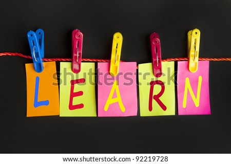 Learn word on laundry hook on black background - stock photo