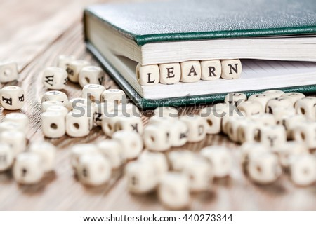 Learn word written on a wooden block in a book. On old wooden table.