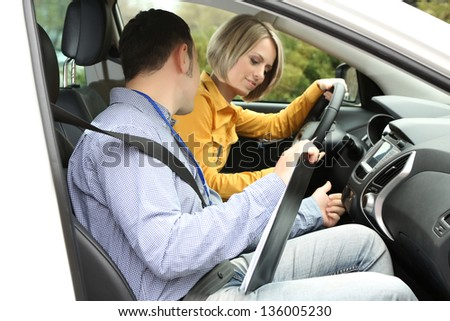Learner driver student driving car with instructor - stock photo