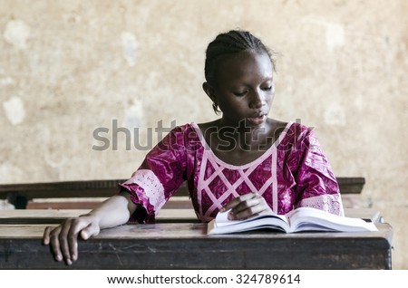 Learning Activity Symbol: Young African girl sitting in classroom reading a book. Education symbol for Africa. Single person studying learning her lesson. - stock photo