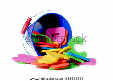 learning concept image of soft foam letters spilling out of a blue bucket.  The bucket is blue and the letters are pink, green, blue and orange and the image is isolated on white, giving copy space. - stock photo