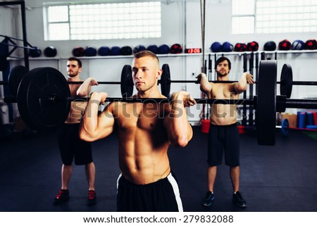 Learning how to do clean and jerk with fitness instructor - stock photo