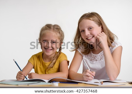 Learning is fun for two young girls sitting in the classroom. Sisters like to learn new information and to develop themselves during lessons in hobby group. Little painters with attractive smiles. - stock photo