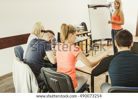 Learning language - English concept. Female teacher tutor near whiteboard screen giving lesson, students making notes. Studies course