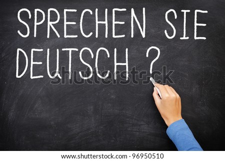Learning language - German. Sprechen Sie Deutch (Do you speak German) written on blackboard. German language class concept showing teacher hand writing in German on chalkboard. - stock photo
