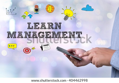 Learning Management System (LMS)  person holding a smartphone on blurred cityscape background - stock photo