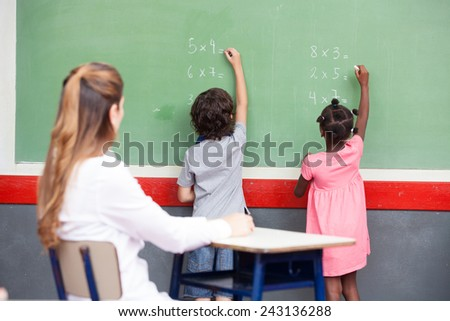 Learning mathematics at elementary school. Multi ethnic students writing on chalkboard with teacher observing. - stock photo