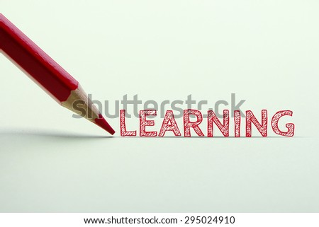 Learning word is standing on the paper with red pencil aside.