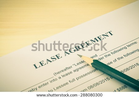 Lease agreement contract sheet and brown pencil at bottom right corner on wood table background in vintage style