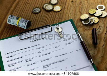 lease agreement money on wood table - stock photo