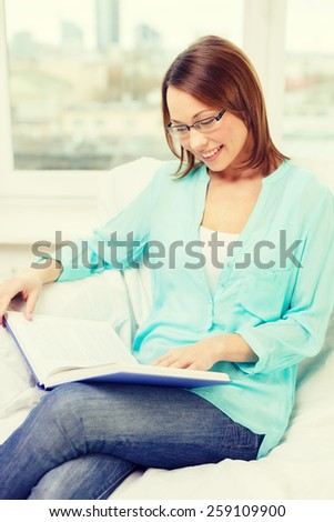 leasure and home concept - smiling woman in eyeglasses reading book and sitting on couch at home