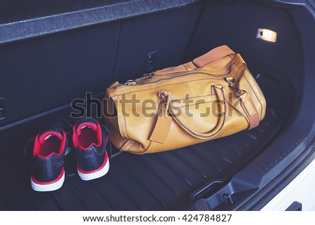 leather bag and sport shoe in car's trunk.