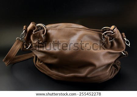 Leather bag on black background. - stock photo