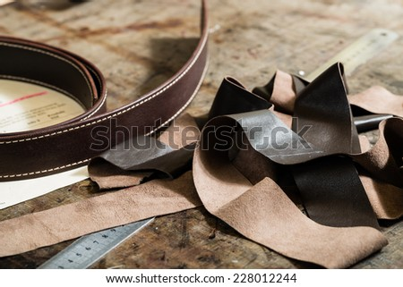Leather belt, iron ruler and remainders of the leather on the working desk in the leather workshop.  - stock photo