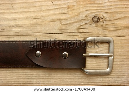 leather belt with a buckle on a wooden board