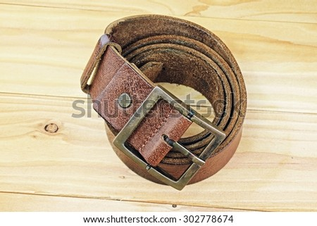 Leather belt with a buckle on a wooden board. Men fashion. Men accessories.  - stock photo
