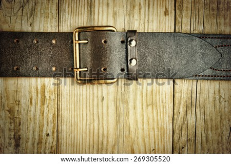 leather belt with a buckle on a wooden board. Toned - stock photo