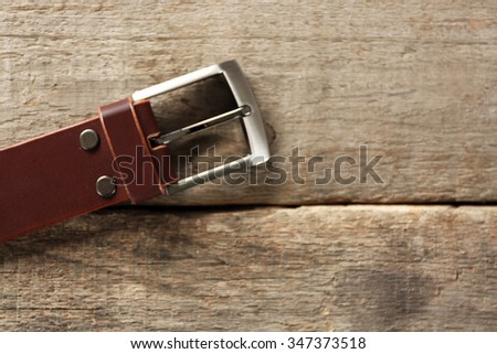Leather belt with buckle on wooden background