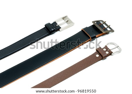 Leather belts in front of a white background