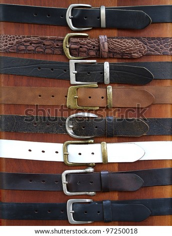 Leather belts on wood background for different uses - stock photo