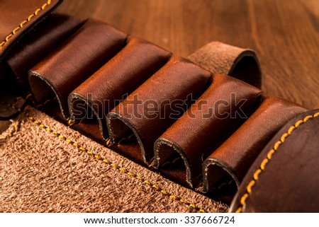 Leather cartridge belt for hunting cartridges on a wooden table - stock photo