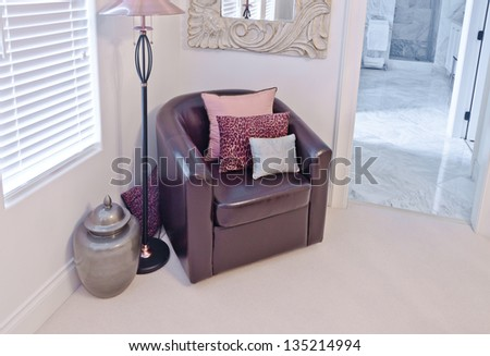 Leather chair with some pillows, floor lamp and the decorative pot in the corner of the room. Interior design. - stock photo