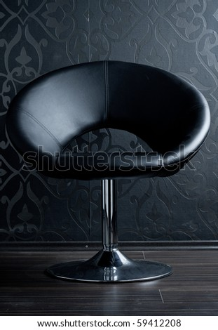 Leather chiar against a wallpapered wall (blue tint) - stock photo