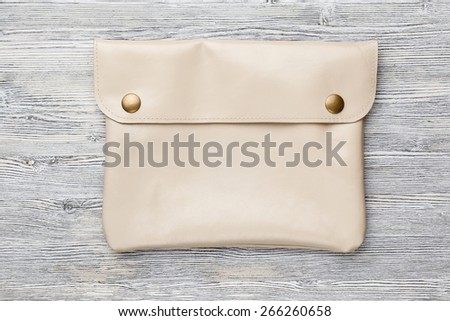 leather clutch bag for tablet on a wooden background - stock photo