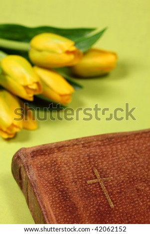 Leather cover Bible with a little golden cross and yellow tulips. Shallow DOF - stock photo