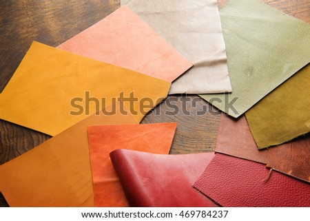 Leather craft. Colorful pieces of beautifully colored or tanned leather on leather craftman's work desk .