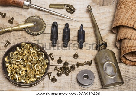 Leather craft tools, buckles and a snake skin roll - stock photo