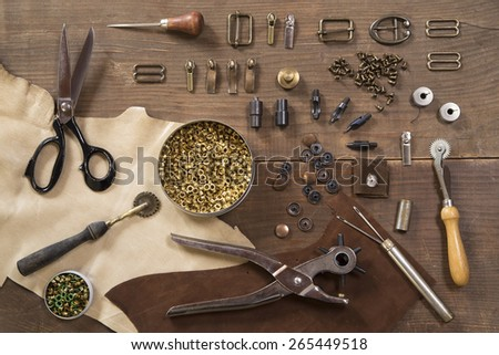 Leather craft tools on a wooden background - stock photo