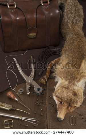 Leather craft tools, stuffed fox and a bag - stock photo