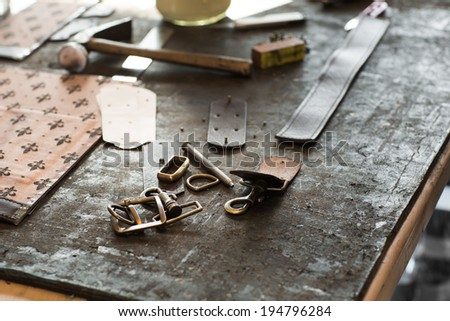 Leather crafting tools on working desk with a low depth of field - stock photo