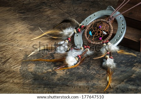 Leather dream catcher and horseshoe on wooden floor - stock photo