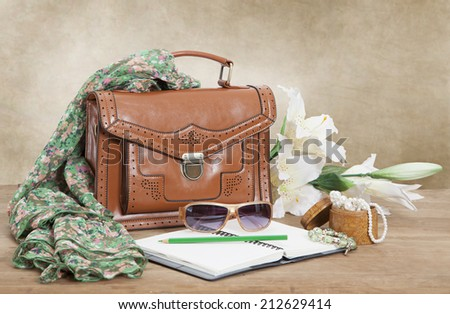 Leather female bag with silk scarf, flowers and accessories  - stock photo