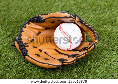Leather Glove With Baseball Ball On Green Pitch - stock photo