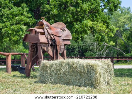 Leather horse saddle displayed on a wooden stand and a hay bale - stock photo