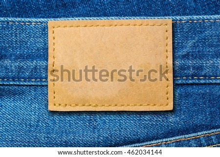Leather label on denim blue jeans fashion background, close up