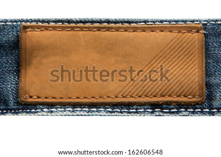 leather label on jeans background isolated on white