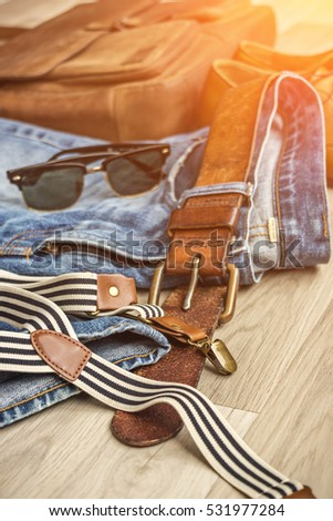 LEATHER LIFESTYLE WITH vintage blue jeans with faded brown leather belt, shoes, messenger bag, sunglasses and suspenders for stylish and modern summer of luxury for casual vintage businessman